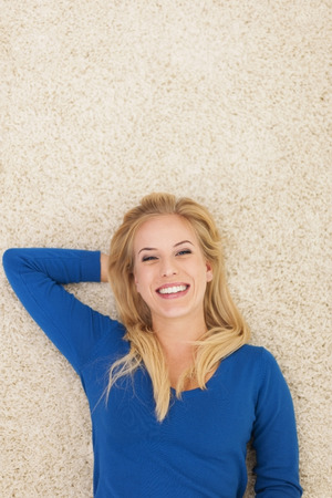 lying on back: Beautiful smiling woman lying down on carpet