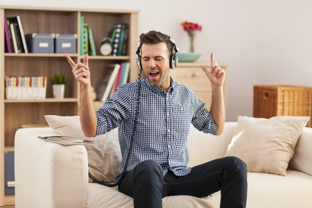 dancing house: Handsome young man sitting on his sofa and listening to music
