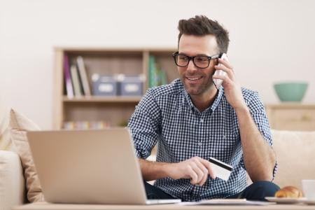 Lachende man maken van bestelling via de mobiele telefoon Stockfoto