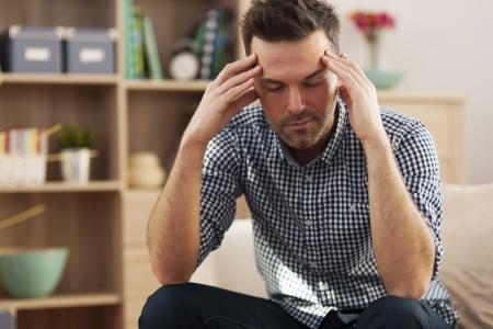 head home: Handsome man sitting on sofa with big headache