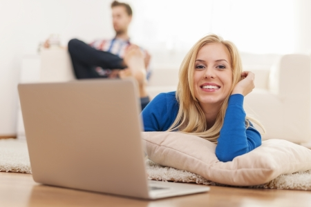 Beautiful blonde woman lying down on carpet at home and using laptop photo