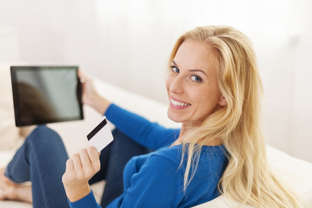 Blonde woman holding digital tablet and showing credit card