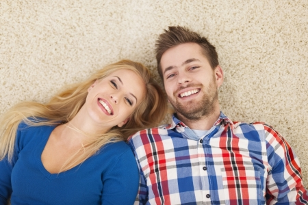 Portrait of happy couple lying down on carpet  photo