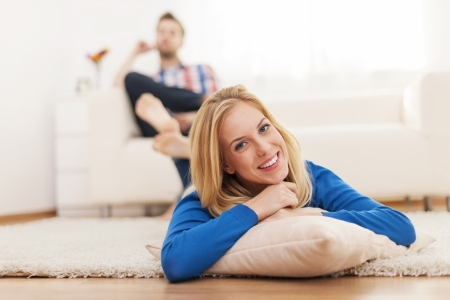 Smiling woman lying down on carpet at home  Stock Photo - 25082341