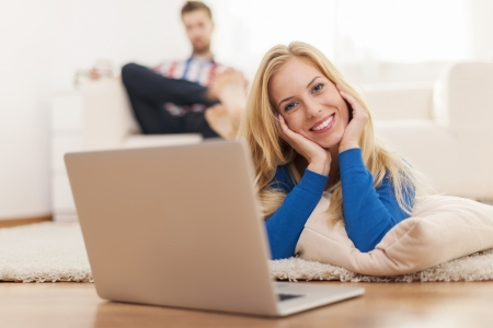 Cute blonde woman relaxing with laptop on carpet at home  photo