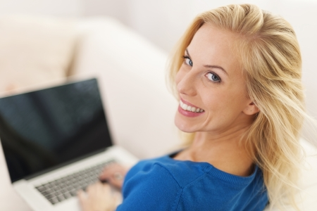 Blonde woman sitting at home with laptop  photo