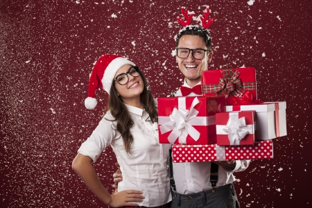 funny glasses: Smiling nerd couple with a lot of christmas presents during the snowing