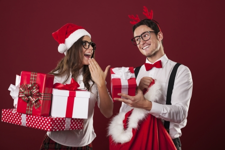 Nerd couple exchanging christmas gifts  Stock Photo
