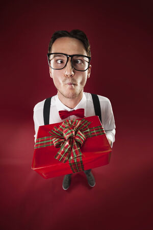 make a gift: Eccentric nerdy man giving christmas present