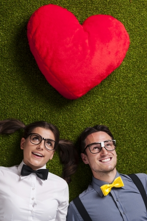 Nerdy couple in love lying down on grass  photo