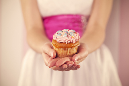 Woman in white dress holding pink muffin  photo