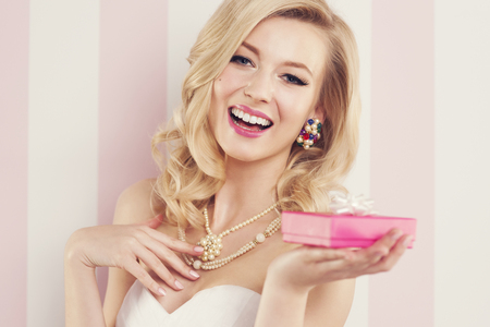 Elegant blonde woman holding pink gift photo