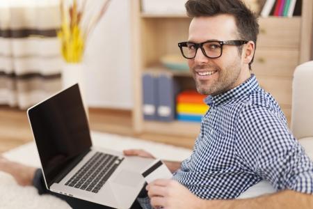 Heureux l'homme avec un ordinateur portable et une carte de cr�dit � la maison photo