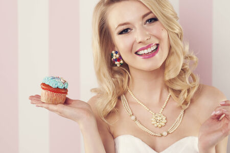 Sensual smiling woman posing with blue muffin  photo