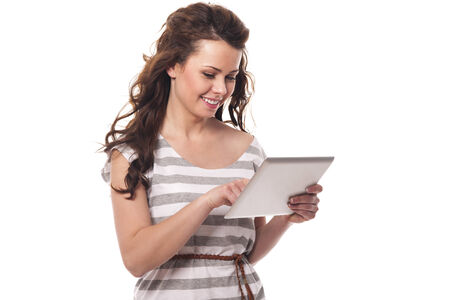 toothy smile: Smiling brunette using digital tablet  Stock Photo