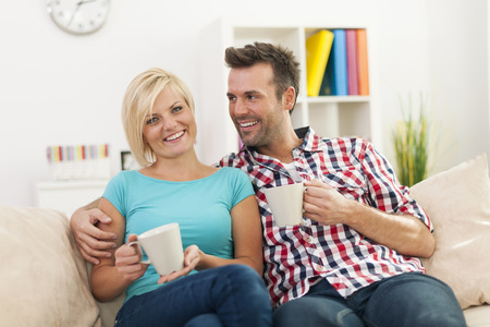 Beautiful couple relaxing on sofa with cup of coffee  Stock Photo - 25230596