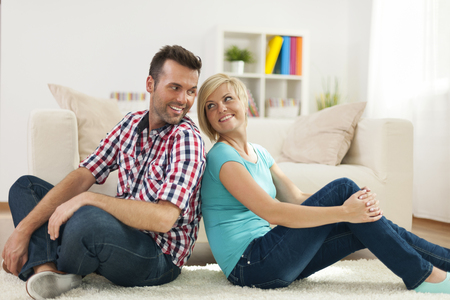 Loving couple sitting on carpet at home Stock Photo - 25232478