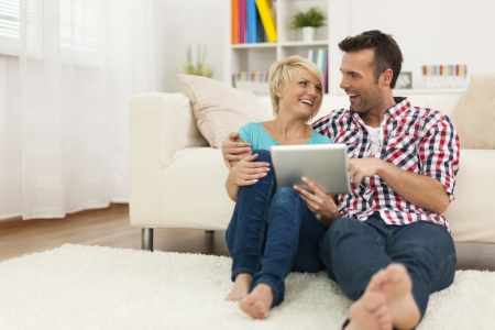 Happy couple sitting on carpet at home and using digital tablet  photo