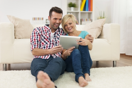 Beautiful couple at home with digital display photo