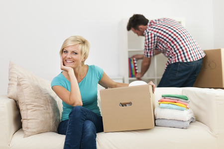 arranging: Portrait of smiling woman during the decorating new living room