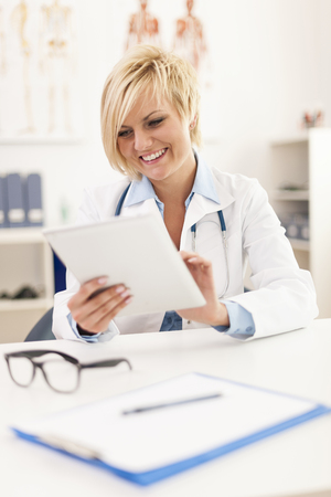 Beautiful smiling female doctor using digital tablet in office  photo
