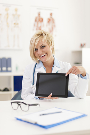 Smiling young female doctor showing on screen of digital tablet photo