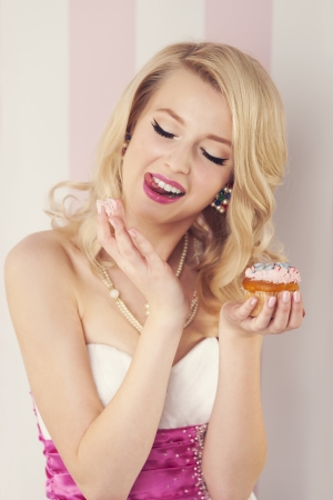 Elegant blonde woman eating cream from muffin  photo
