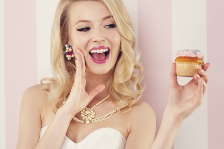 Excited elegant woman with muffin  photo