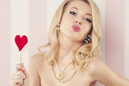 Sexy woman with lollipop in heart shaped blowing kisses  photo