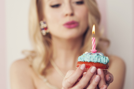 Sexy blonde woman blowing candle  photo