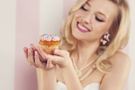 Sourire femme blonde tenant un petit muffin photo