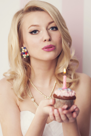 Beautiful blonde woman celebration with muffin and candle  photo