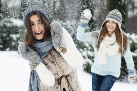 Young women have fun during the snowball fight photo