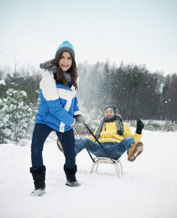 Couple have fun on sled in winter time  photo