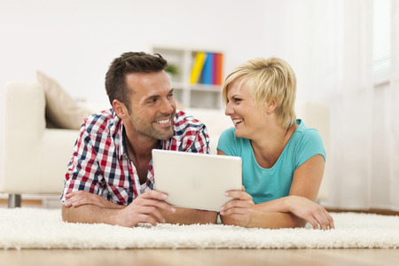 Loving couple with digital tablet on carpet  photo
