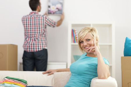 Woman sitting in new home and man decorating living room photo