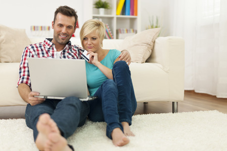 house shopping: Couple sitting on carpet at home and doing shopping online