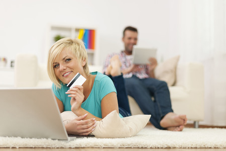 Beautiful blonde woman relaxing at home with laptop and credit card photo