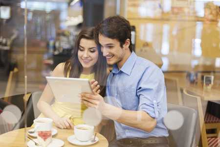 Beautiful couple using digital tablet in cafe  photo