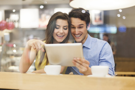 Excited couple with digital tablet in cafe  photo