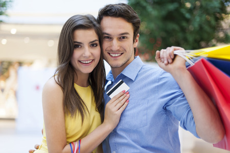 Portrait of smiling couple with credit card and shopping bags photo