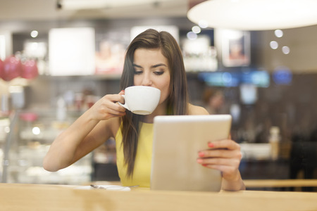 Beautiful woman in cafe using digital tablet  photo