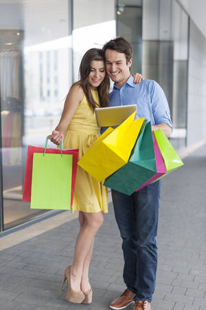 Fashion couple using digital tablet during the shopping  photo