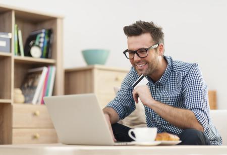 Gelukkig man zit op de bank met laptop en credit card