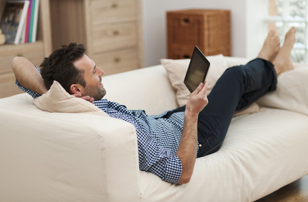 barefoot man: Man relaxing with digital tablet at home