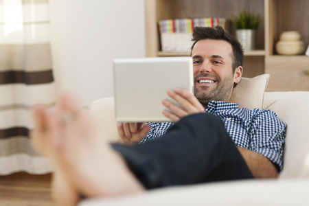 barefoot man: Smiling man lying on sofa with digital tablet