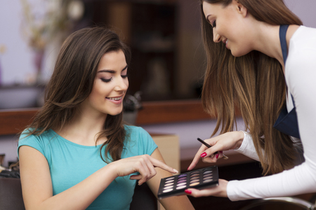 Woman with makeup artist choosing color of eyeshadow photo