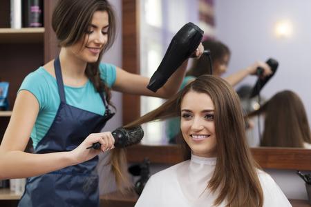 Peluquería femenina usando cepillo y secador de pelo Foto de archivo - 25931259