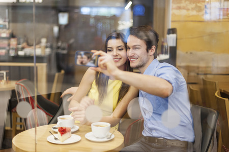 Beautiful couple taking selfie photo in cafe  photo