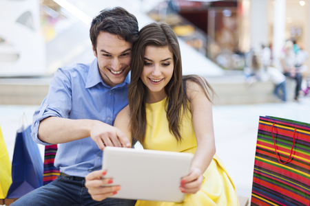 Beautiful couple in shopping mall looking on digital tablet  photo